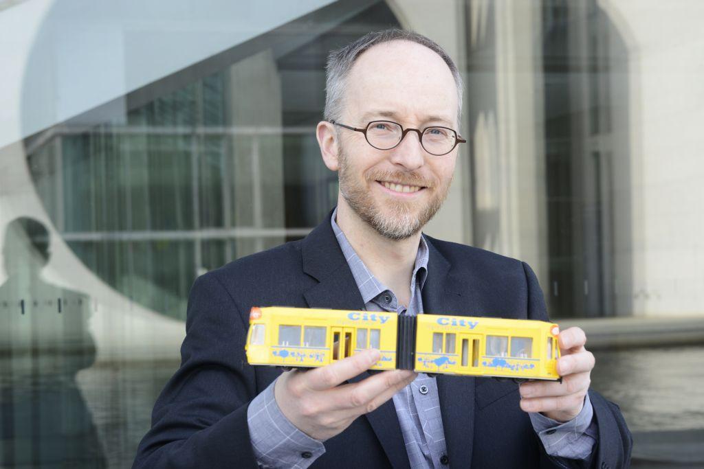 Matthias Gastel hält eine Straßenbahn in seinen Händen