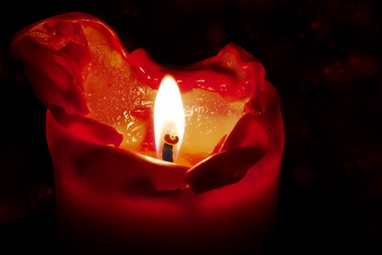 red candle with flame and melting wax against a dark background