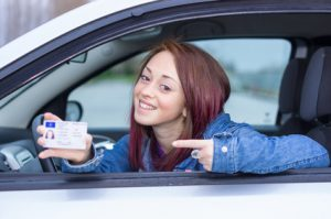 Attractive caucasian girl showing her driver license