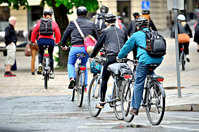 Bicyclists on their way home in the rain, properly dressed with helmets and gear